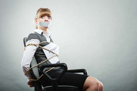 Afraid businesswoman bound by contract terms and conditions with mouth taped shut. Scared woman tied to chair become slave. Business and law concept.