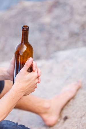 alcoholismo: El hombre deprimido que sostiene la botella de vino que se sienta en la orilla del mar al aire libre. La gente abuso y problemas de alcoholismo Foto de archivo