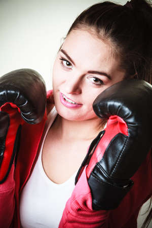 emancipation: Emancipation and feminist. Defense concept. Young fit woman boxing on gray background in studio.