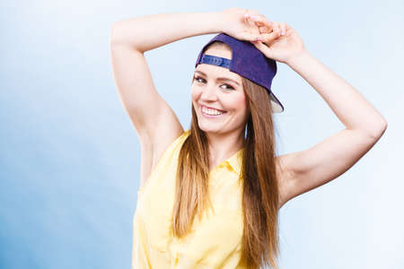 Woman casual style teen girl cap on head long hair posing on blue. Youth style. Fashion shot.