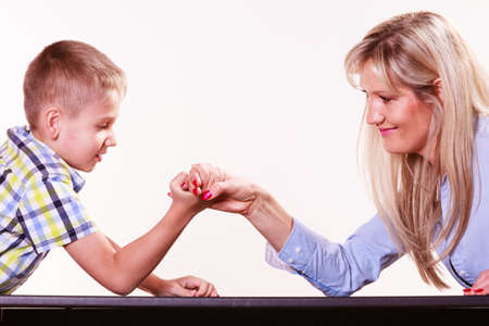 upbringing: Spending time with family fun and family bonds. Mother and son arm wrestle and have fun indoors.