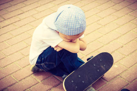 rejection sad: Lonely sad child boy with skateboard. Depressed sullen kid. Loneliness, solitude and rejection concept.