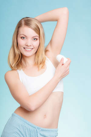 underarms: Daily skin care and hygiene. Girl applying stick deodorant in armpit. Young woman putting antiperspirant in underarms on blue
