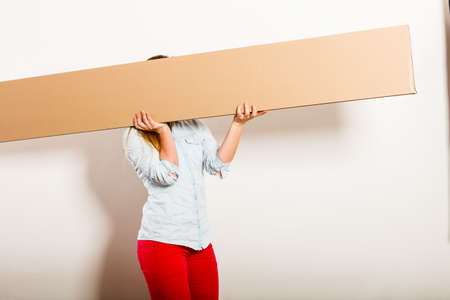 moving box: Woman moving into new apartment house carrying carton box with furniture. Girl arranging interior and unpacking.