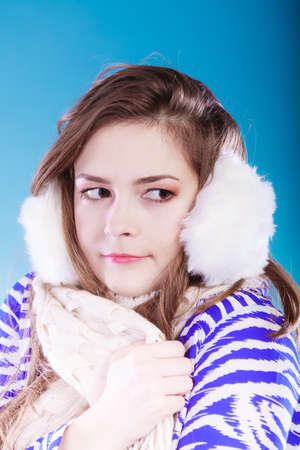 muff: Teenage girl wearing fluffy white earmuff in winter fashion, cold time. Stock Photo
