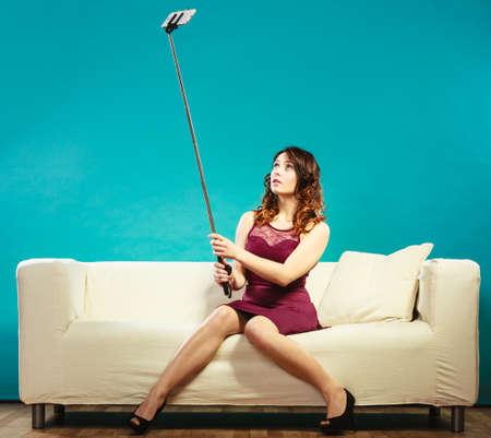 기술 인터넷 및 행복 개념입니다. 집에서 소파에 앉아있는 동안 스틱에 스마트 폰 카메라로 자기 사진 셀카를 복용하는 젊은 여자 재밌는 소녀