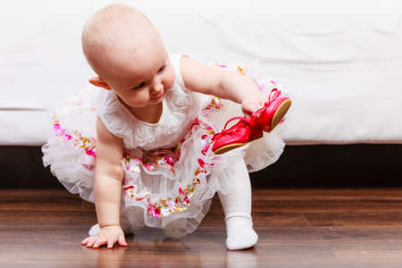 girl squatting: Lesson of walking. Sweet adorable baby girl making steps at home. Little child toddler wearing princess dress with red small shoes. Stock Photo