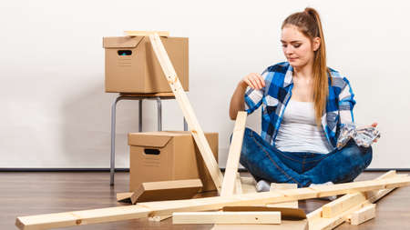 arranging: Worried woman moving into new apartment house assembling. Young girl holding screws and furniture parts arranging interior and unpacking boxes.