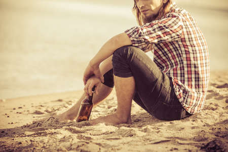 alcoholismo: Man depressed with wine bottle sitting on beach outdoor. People abuse and alcoholism problems Foto de archivo