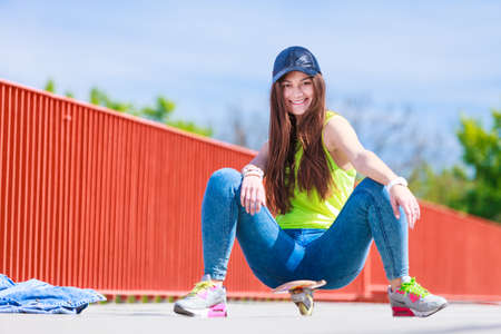 fun activity: Summer sport and active lifestyle. Cool teenage girl skater riding skateboard on the street. Outdoor.