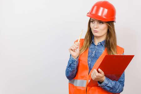 Il engineerin strutturale del costruttore del muratore della donna nel casco duro rosso della maglia arancio tiene il cuscinetto dell'archivio di penna. Sicurezza nel lavoro industriale Studio girato Archivio Fotografico - 56071069