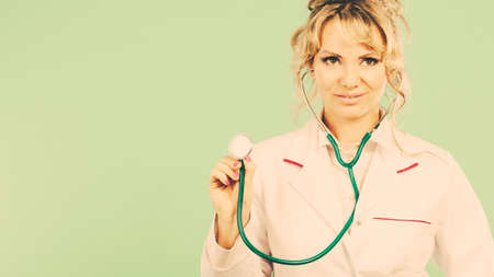beating: Medical examinations concept. Doctor pediatrician with stethoscope listening heart beating. Female physician holding professional medic tool.