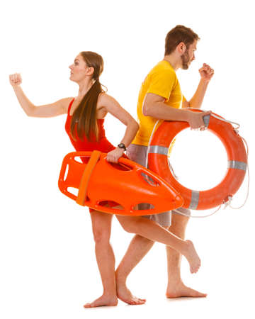 float tube: Lifeguards running with rescue tube and ring buoy on duty. Man and woman supervising swimming pool. Accident prevention. Stock Photo