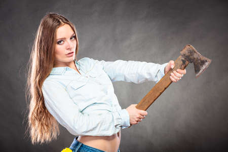 axe girl: Sexy seductive woman holding axe chopper. Strong girl feminist working in man profession. Independent female. Studio shot. Stock Photo