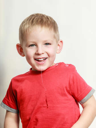 saliva: Free time, fun and expression. Little boy play indoors make silly face emotions drool. Blonde child in red shirt saliva spilling from the mouth