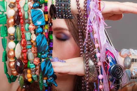 plentiful: Pretty young woman wearing bracelets holding many plentiful of precious jewelry necklaces beads. Portrait of gorgeous fashion girl in studio on gray. Stock Photo
