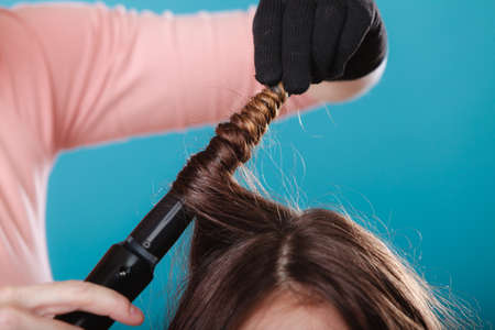 curler: Hairdresser curling woman hair with electric iron curler tong. Hairstylist making girl hairstyle. Beauty.