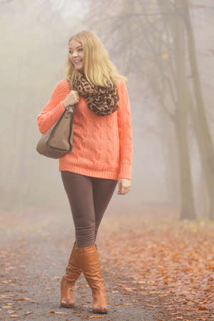 pullover: Fashionable woman posing in foggy autumn park. Pretty young girl in sweater pullover with handbag in forest. Fall fashion vogue.