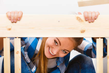 self assembly: Happy woman having fun assembling wood furniture. DIY enthusiast. Girl doing home improvement. Stock Photo