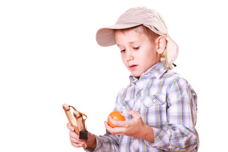 prankster: Nature and free time prankster little boy. Child have fun with  wooden sling shot and fruit hold orange. Stock Photo