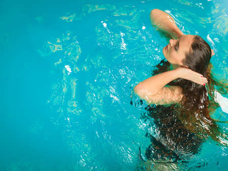 floating on water: Woman relaxing at swimming pool. Young girl wearing black dress floating. Water aerobics fitness. Stock Photo
