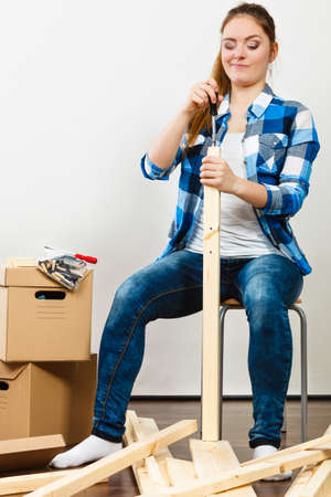 self assembly: Woman moving into new apartment house assembling furniture with screwdriver. Young girl sitting on chair arranging interior and unpacking boxes.