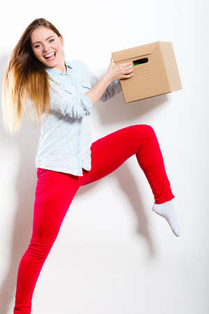 moving box: Happy woman moving in carrying carton box. Young girl arranging interior and unpacking at new apartment house home.