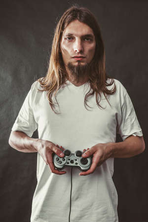 dependency: Addiction and dependency concept. Young man with pad joystick playing games. Male addicted to console playstation videogames.
