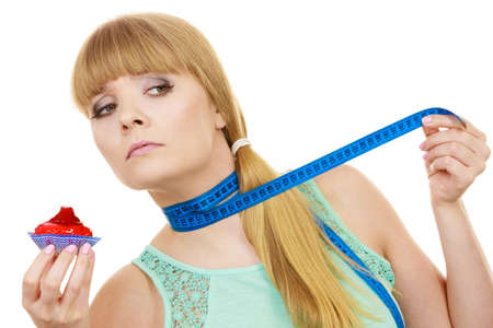 resist: Woman undecided with blue measuring tape around her neck holds in hand cake cupcake, trying to resist temptation. Weight loss diet dilemma gluttony concept.