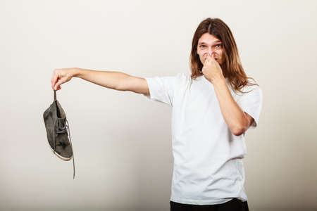 unpleasant smell: Young long haired man male wearing white t-shirt holding dirty stinky sweaty shoe in one hand fingers. Unpleasant smell stink.