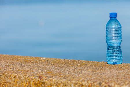 refrescar: botella de plástico de agua al aire libre en la orilla del mar nadie