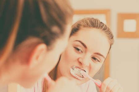 higiene bucal: Mujer cepillarse los dientes de limpieza. Chica con cepillo de dientes en el ba�o mirando al espejo. Higiene oral. foto filtrada