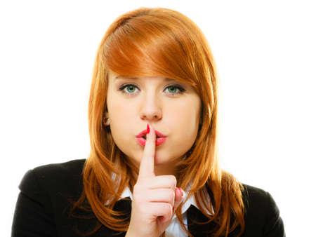 secrecy: Business woman redhaired girl asking for silence or secrecy with finger on lips hush hand gesture. Isolated Stock Photo