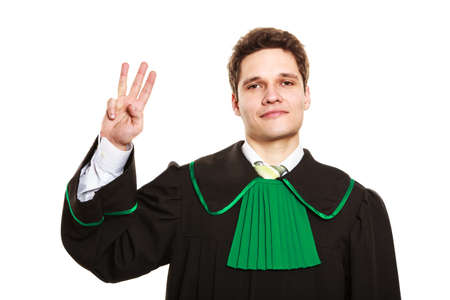 toga: Comprender y explicar el env�o de un mensaje claro. joven abogado desgaste toga esmalte y mostrar signo de la mano. El hombre hace gesto de sostener tres dedos en el aire.