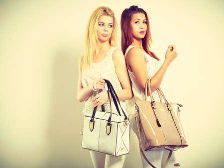 prendas de vestir accesorios de moda para damas. Una foto de dos jóvenes modelos con bolsos de mano. niñas atractivas vistiendo la misma ropa blanca.