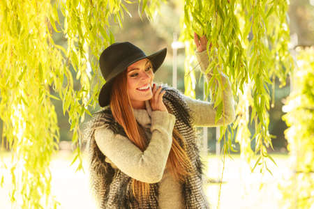 someone: Meeting time. Trendy young woman waiting for someone in park waving her hand around green leaves of willow tree. Stock Photo