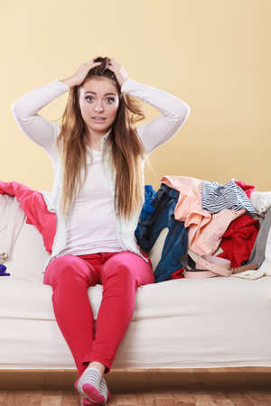 messy room: Desperate helpless woman sitting on sofa couch in messy living room with hands on head. Young girl surrounded by many stack of clothes. Disorder and mess at home.