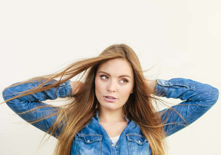 girl  care: Female fashion and haircare. Fashionable young attractive woman wearing denim jeans shirt. Girl with brown long hair waving on air. Lady take care of hairdo.