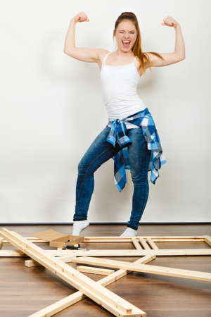 self assembly: Successful and strong woman moving into new apartment house with furniture to assembly. Young girl showing off muscles. Success and achievement.