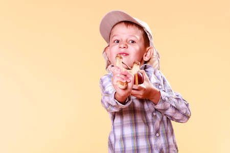 prankster: Nature and free time prankster little boy. Child have fun with  wooden sling shot and fruit aim apple. Stock Photo