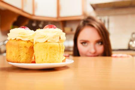 Femme se cachant derrière la table se faufiler et en regardant délicieux gâteau à la crème douce et de fruits sur le dessus. Appétit et le concept de la gourmandise.