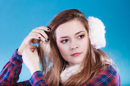 muff: Young woman wearing fluffy white earmuff. Teenage in cold time. Stock Photo