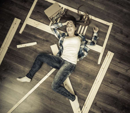 self assembly: Happy woman having fun assembling furniture at home. Young girl laying on floor arranging apartment house interior. DIY. High angle view. Stock Photo