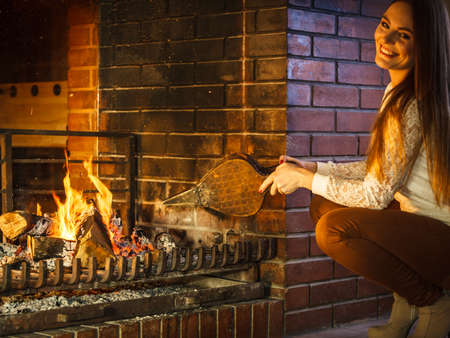 Woman at fireplace making fire with bellows. Young girl heating warming up and relaxing. Winter at home. Stock Photo