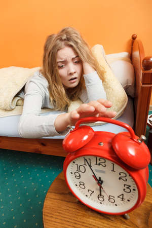 oversleep: Exhausted woman waking up in bed turning off alarm clock. Young girl in the morning. Stock Photo