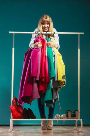 grabbing: Funny happy woman girl taking grabbing all clothes coats and shirts in wardrobe. Young girl shopping in mall. Fashion clothing sale concept.