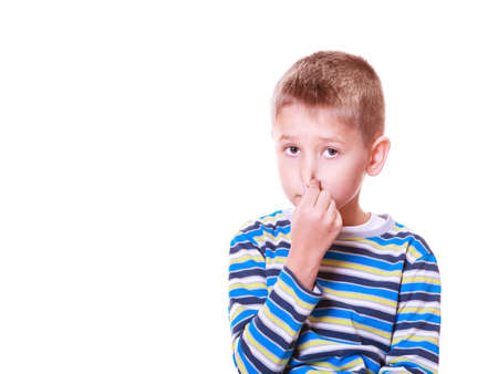 Expression and emotions react to sourrandings. Little boy cover nose with fingers smell. Stock Photo