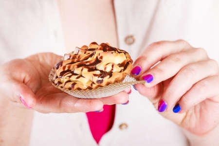 gluttony: Delicious tasty sweet cake cupcake in human hands. Gluttony concept.