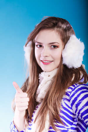 earmuff: Smiling teenage girl wearing fluffy white earmuff in winter fashion. Giving thumbs up sign. Stock Photo