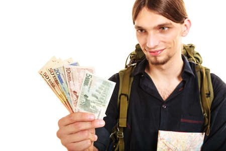 thrifty: Man tourist backpacker holding euro money and map. Young guy hiker backpacking. Summer vacation travel. Isolated on white background. Stock Photo